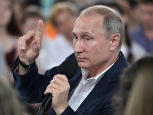 На фото президент РФ Путин участвует в пресс-конференции отвечая на вопросы граждан и журналистов.